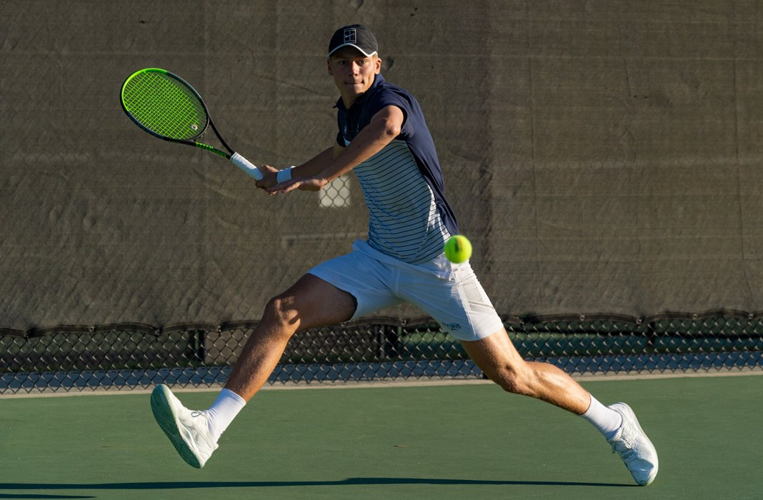 Luke Simkiss of Keiser University men's tennis keeps his eye on the ball for a return during the men's singles final at the 2020 ITA Cup
